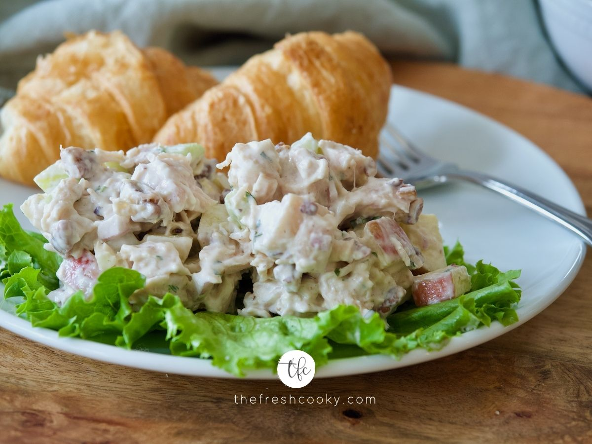 Plate with chicken tarragon salad on lettuce leafs with croissants on back of plate.