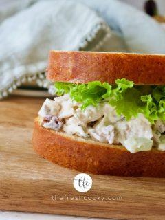 Chicken Salad Sandwich between Brioche Bread with lettuce leaf in between.