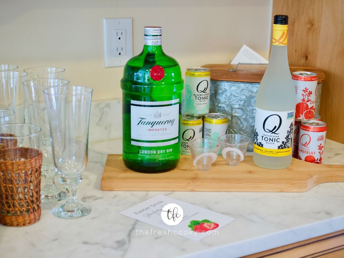 Cocktail Station set up for Strawberry Gin Cocktail. Glasses, on cutting board Gin, tonic waters, measuring cup and instructions.