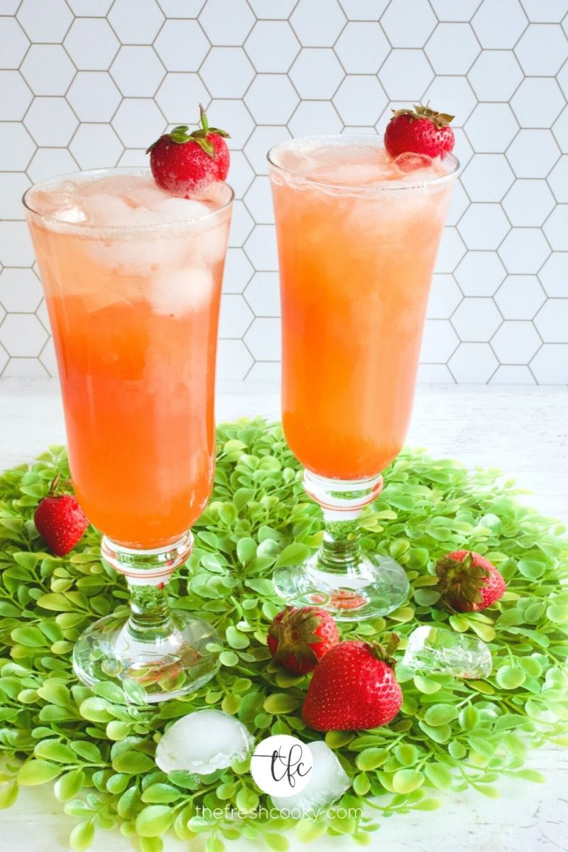 Two pretty tall glasses with strawberry gin and tonic on bed of fake leaves with strawberries and ice cubes.