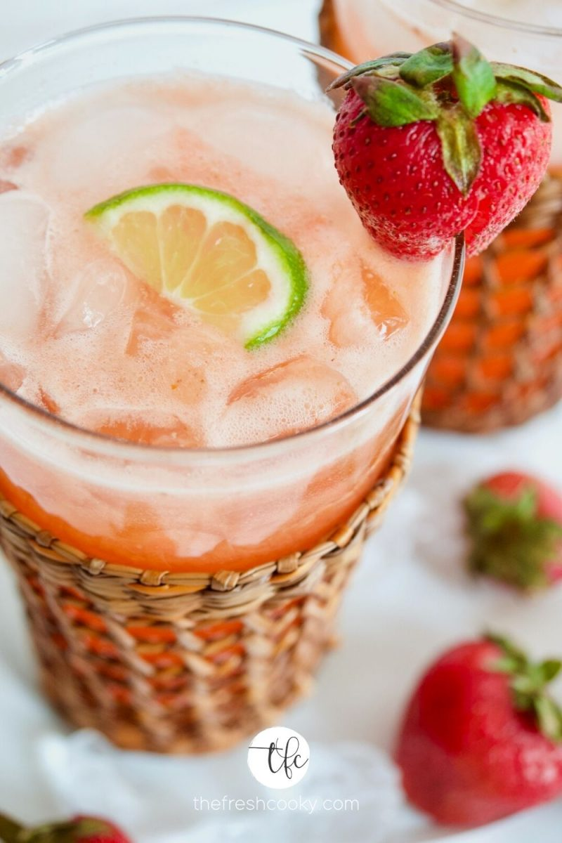 CLose up image of strawberry gin cocktail with wedge of lime and strawberry in a tall wicker jacketed glass.