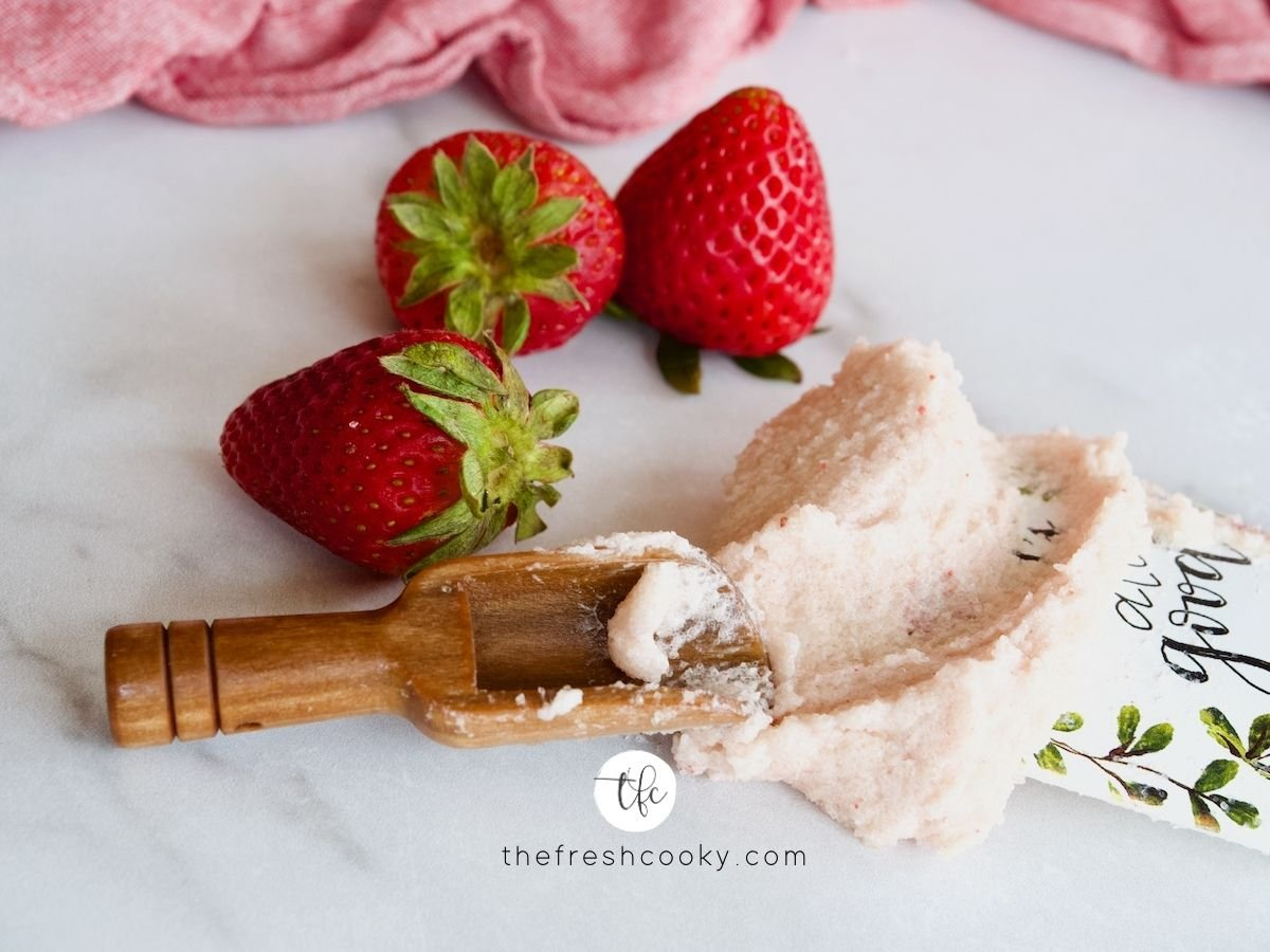 Shmear of strawberry sugar scrub with wooden scoop and 3 fresh strawberries behind.