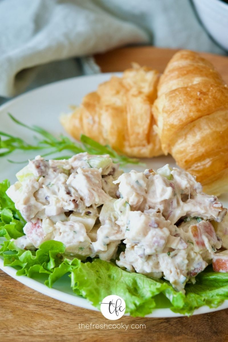 Tarragon Chicken Salad on a bed of lettuce with croissants behind.