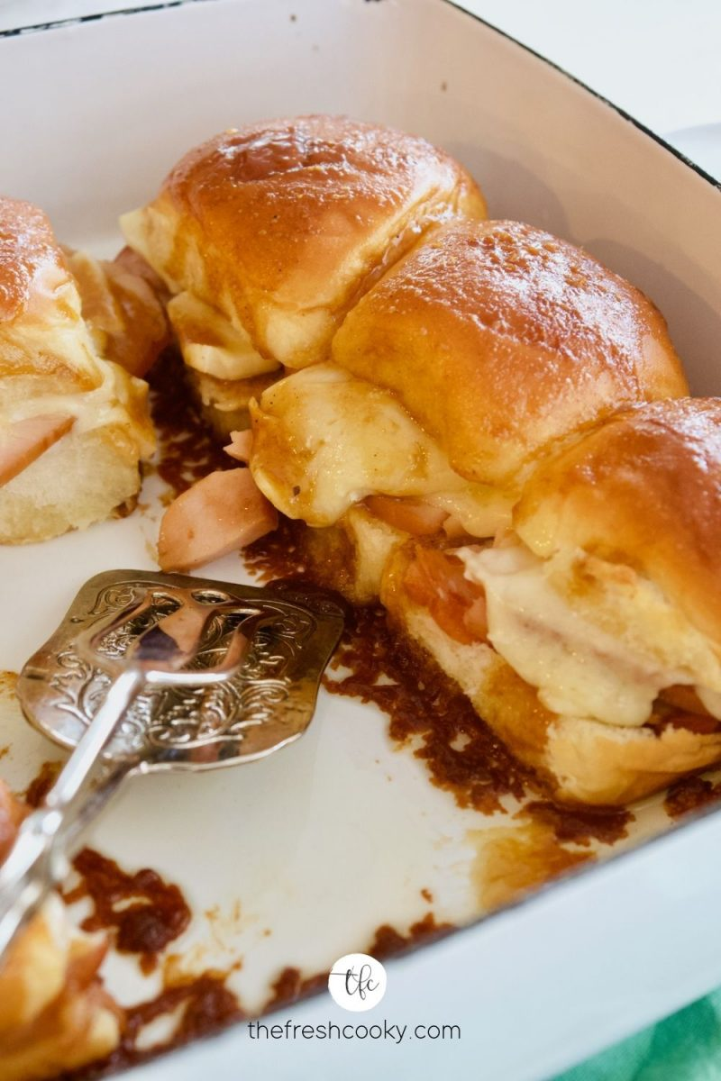 Pan with two sliders removed and serving tongs inside with gooey cheesy turkey sliders waiting to be eaten.