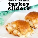 Pinterest image for Hawaiian Roll Turkey Sliders with two sliders on a plate and pan of sliders in background.