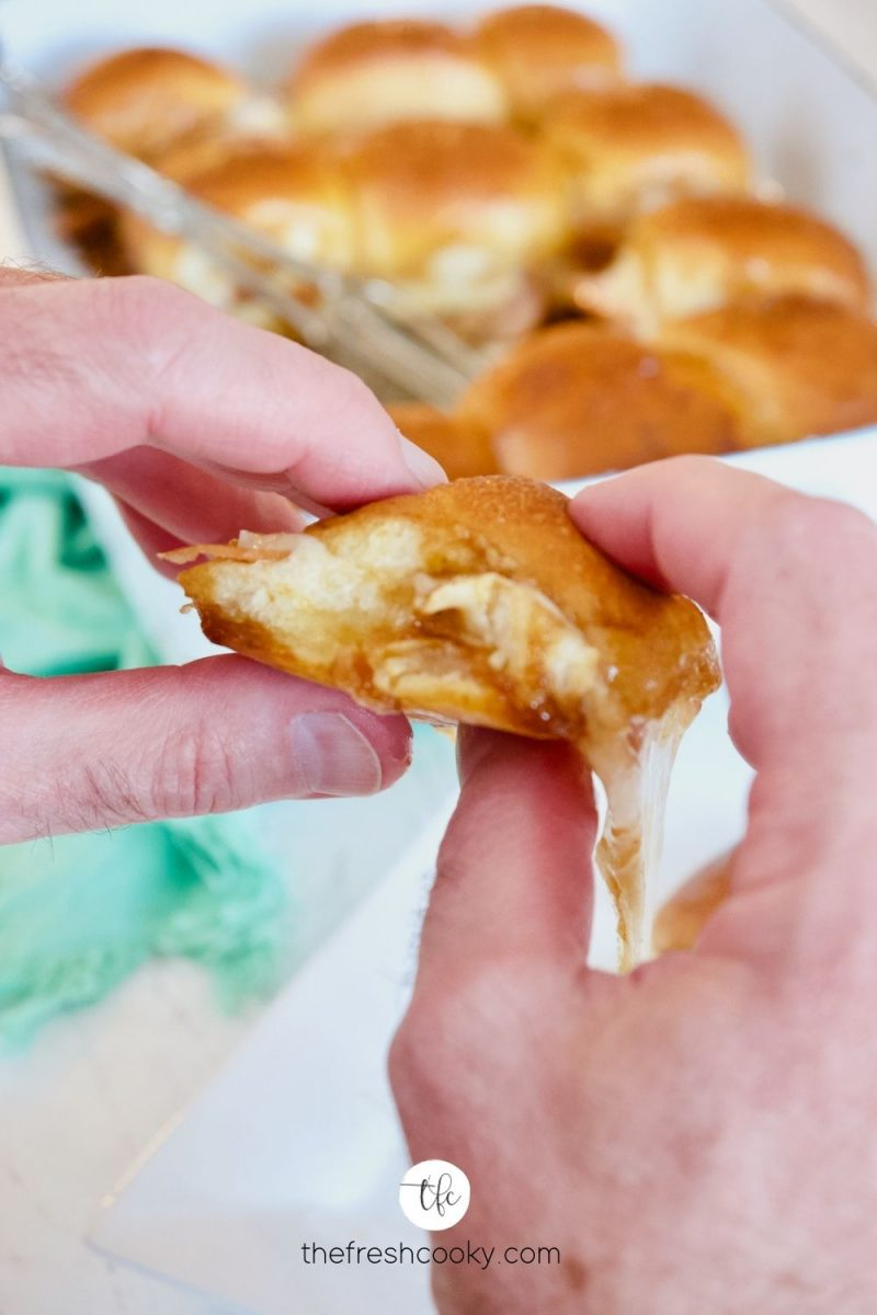 Hands holding a turkey slider sandwich with dripping gooey cheese and tray of sliders behind.
