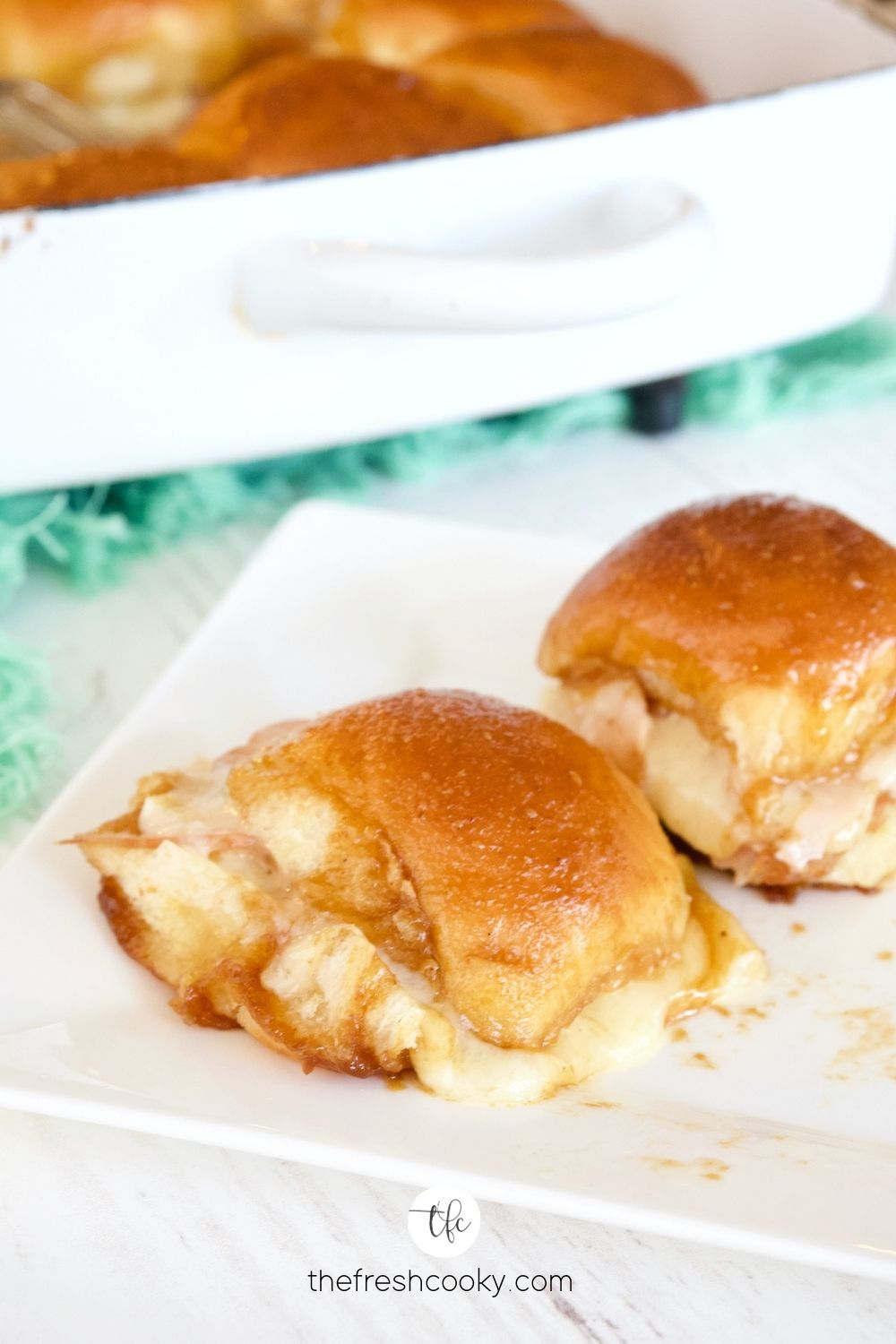 Two gooey Turkey and Cheese Sliders on white plate with casserole behind.
