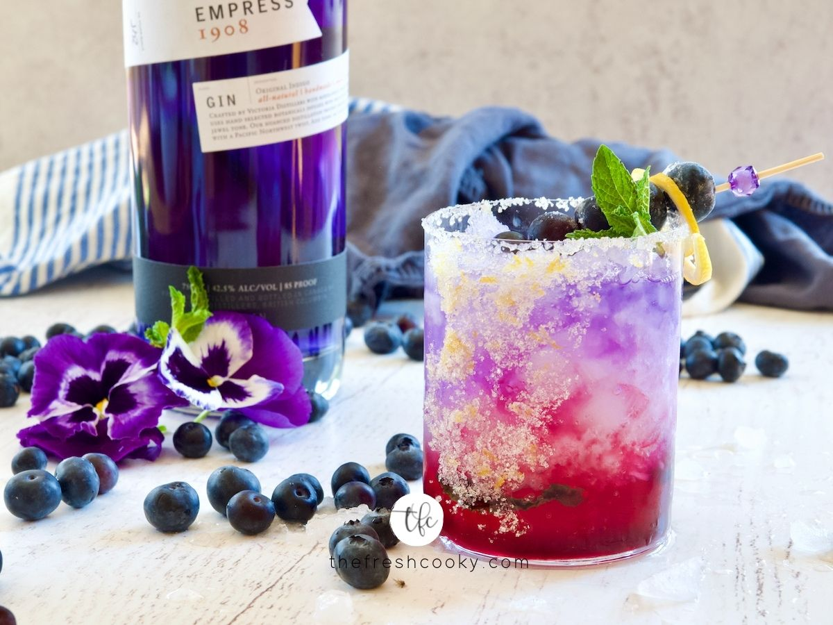 Blueberry Gin Cocktail with lemon sugar rim and bottle of Empress Gin in backgroudn with pansies and blueberries.