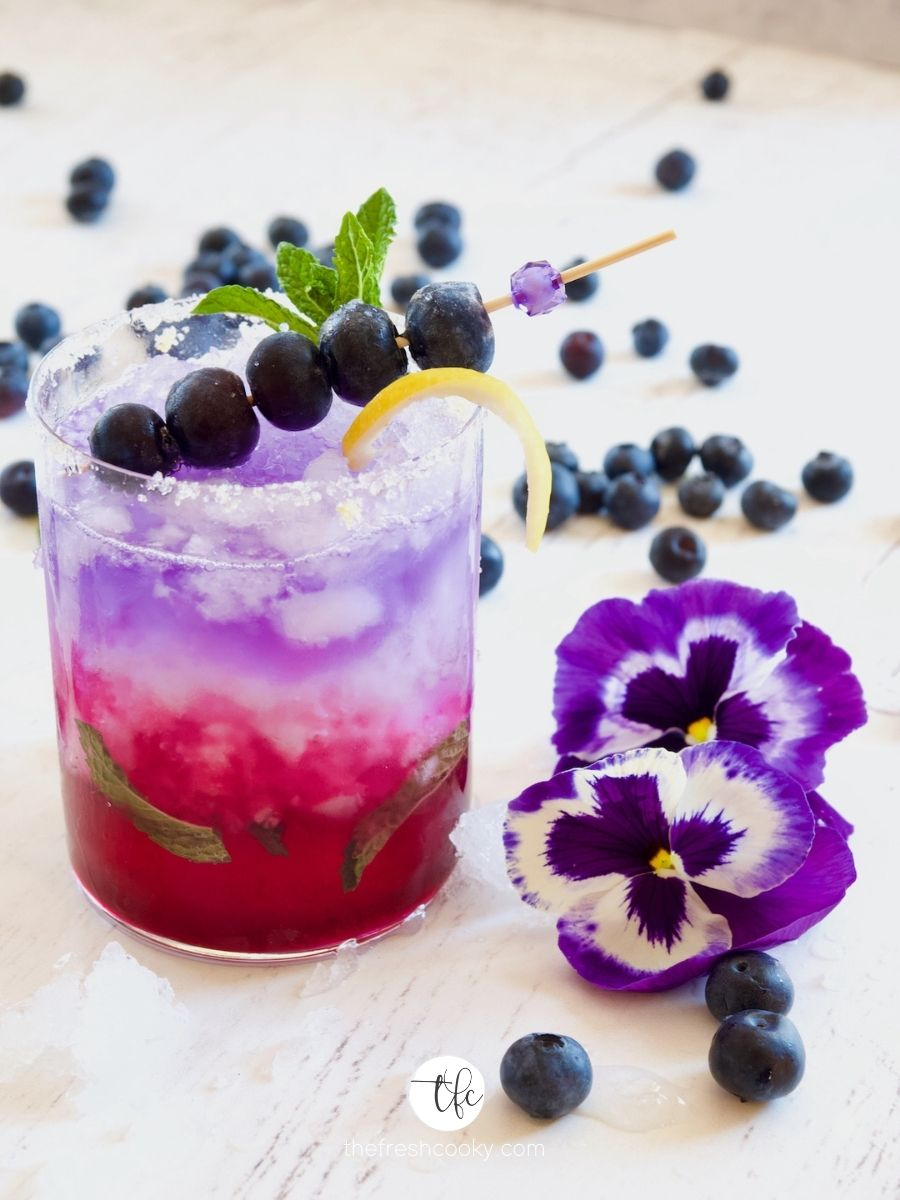 Image of a bluebuerry gin fizz with pansies and blueberries strewn about.
