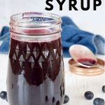 Pin for easy fresh blueberry syrup with closeup of jar of blueberry syrup with spoon in background and fresh blueberries around.