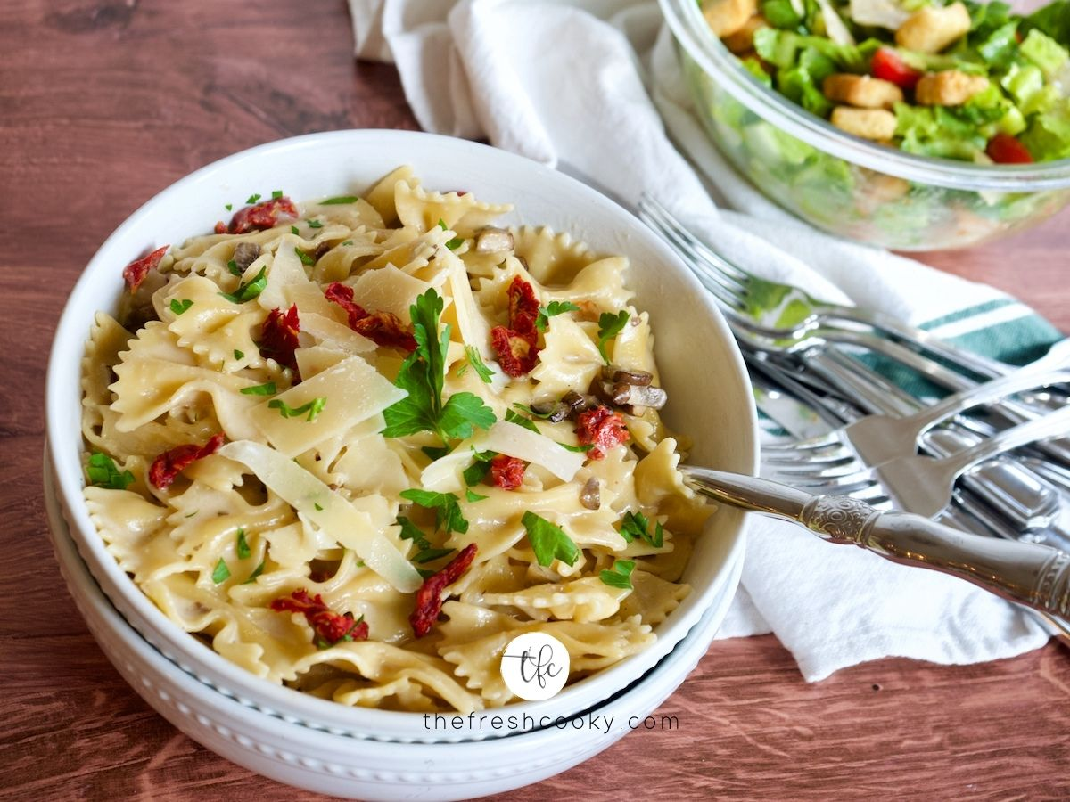 Creamy Bow Tie Pasta with Sun-dried tomatoes in large pasta bowl with salad in background.