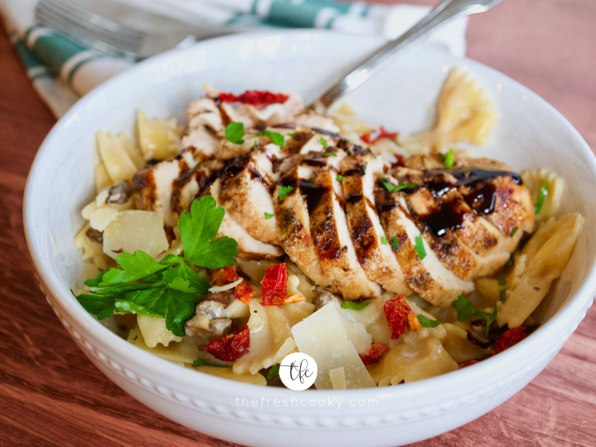 Creamy Tuscan Pasta with sun-dried tomatoes and mushrooms with sliced chicken on top.