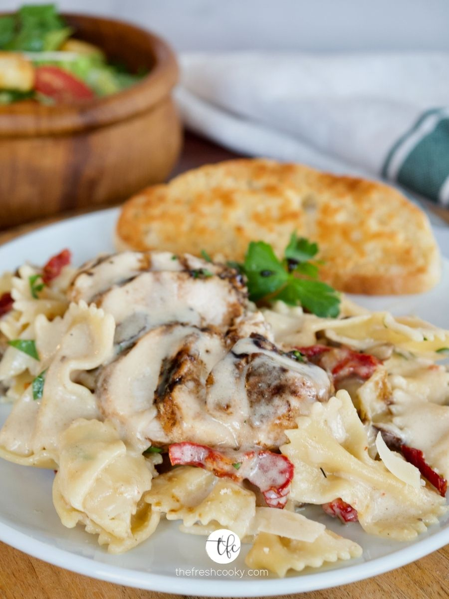Creamy Bow Tie Pasta on white plate with garlic toast and a salad in background.