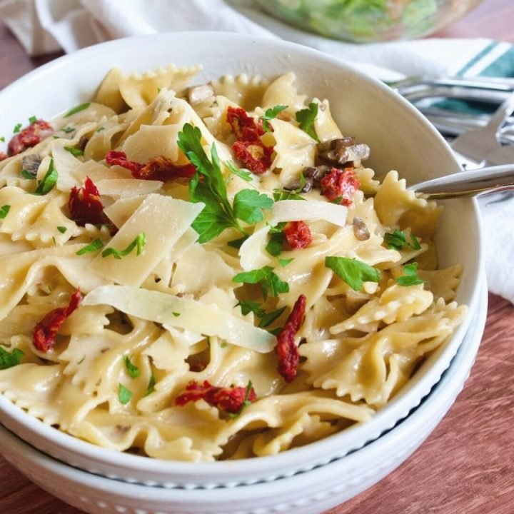 creamy bow tie pasta recipe with sun-dried tomatoes and mushrooms in large bowls with spoon.