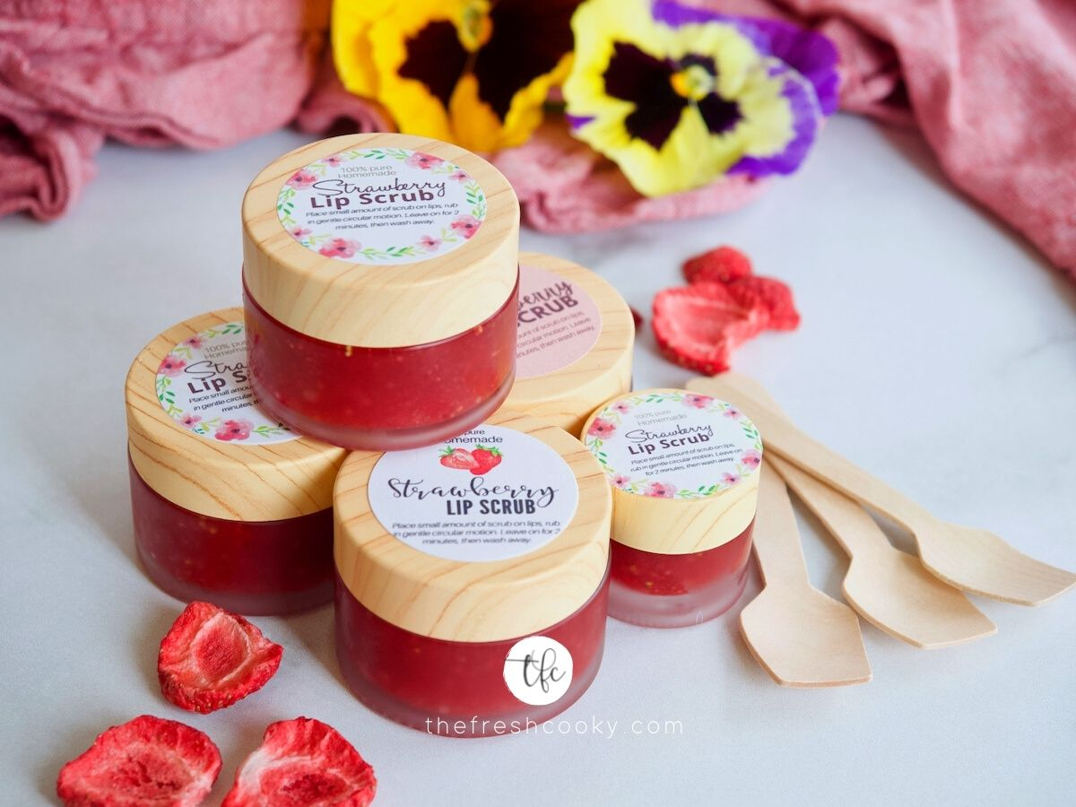 Facebook image for DIY Lip Scrub in little pots with pretty labels, small wooden scoops beside.