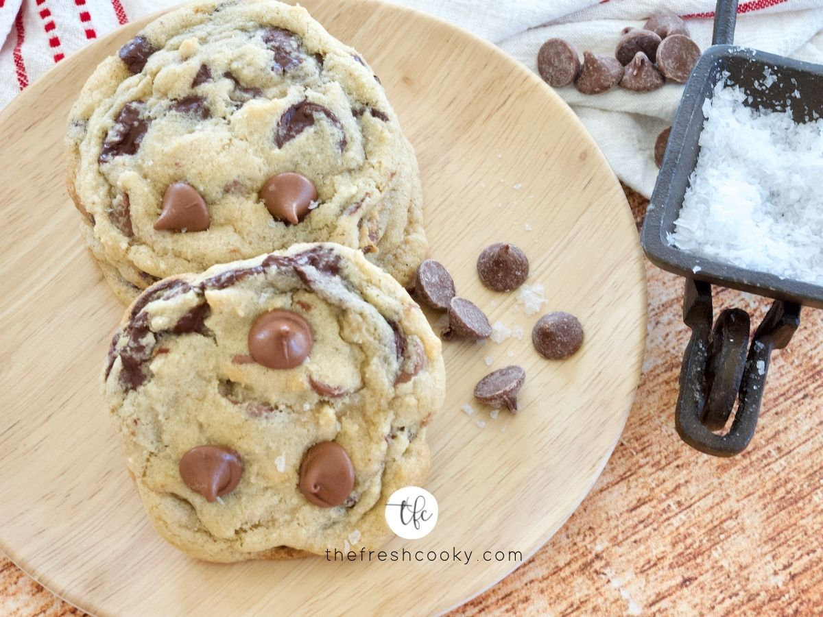Best chewy gf chocolate chip cookies on wood grain plate with a small bowl of flaky sea salt nearby.