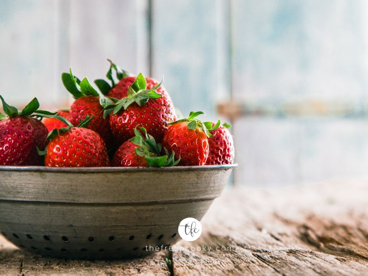 strawberries in a bowl on a rustic table.