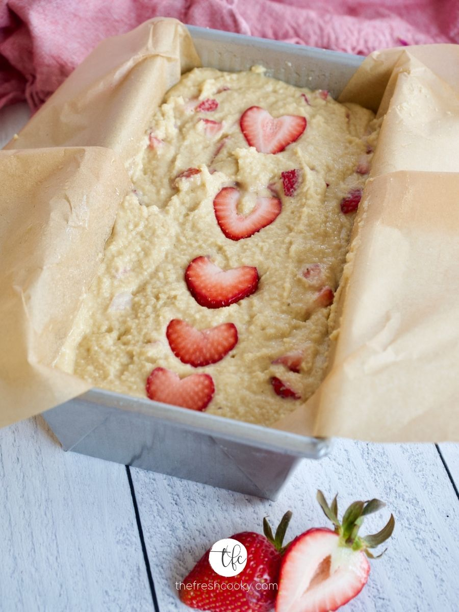 """Smoothed out Strawberry Bread batter in loaf pan with sliced strawberry """"hearts"""" on top ready for baking."""