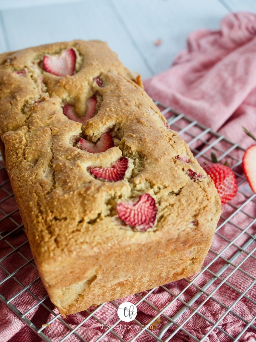 Image of gluten free, dairy free, sugar free Strawberry Quick Bread on wire rack with strawberries nearby.