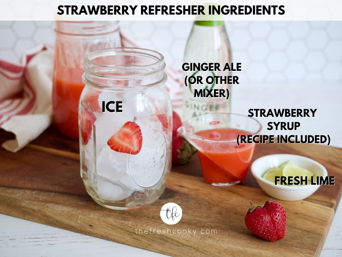 ingredients for strawberry refresher, glass with ice, lime, ginger ale, strawberry syrup.