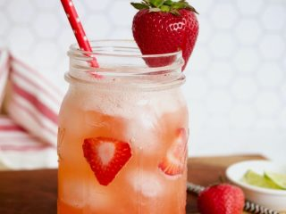 Gorgeous shot of strawberry refresher drink on wooden cutting board with pink straw and a strawberry garnish with limes and strawberries in the background.