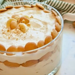 Large glass bowl filled with Magnolia Banana Pudding with a green and white striped towel in background.