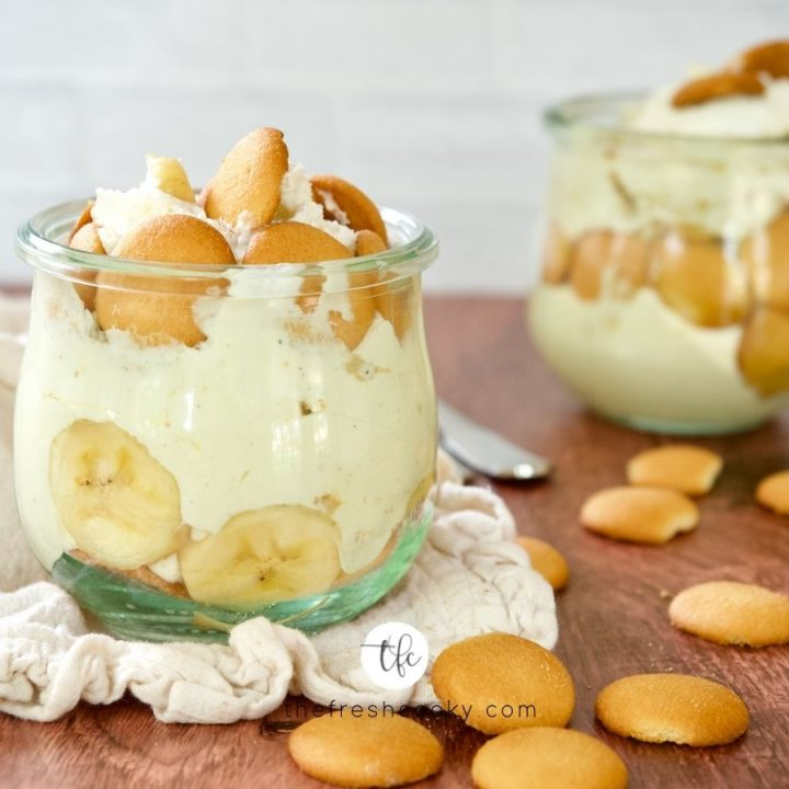 Best Magnolia Banana Pudding in small jars with nilla wafers laying on table.