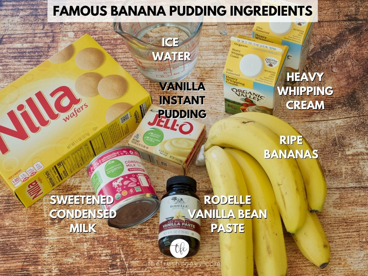 Ingredients on a wooden board for Magnolia Banana Pudding l-r Nilla wafers, ice water, heavy cream, bananas, Rodelle Vanilla Bean paste, sweetened condensed milk and Jell-O Instant Vanilla Pudding mix.