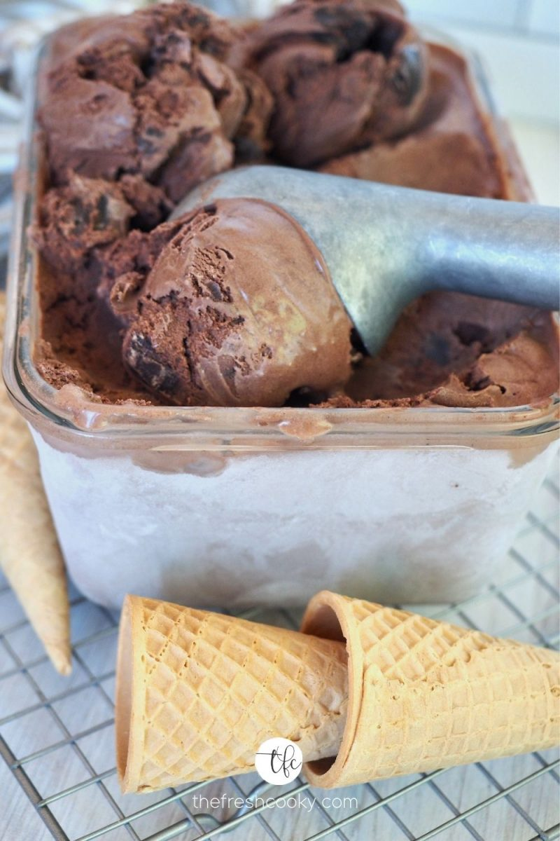 Frozen rectangler container with ice cream scoop scooping large creamy scoop of Chocolate Brownie Fudge Ice Cream with sugar cones in front.