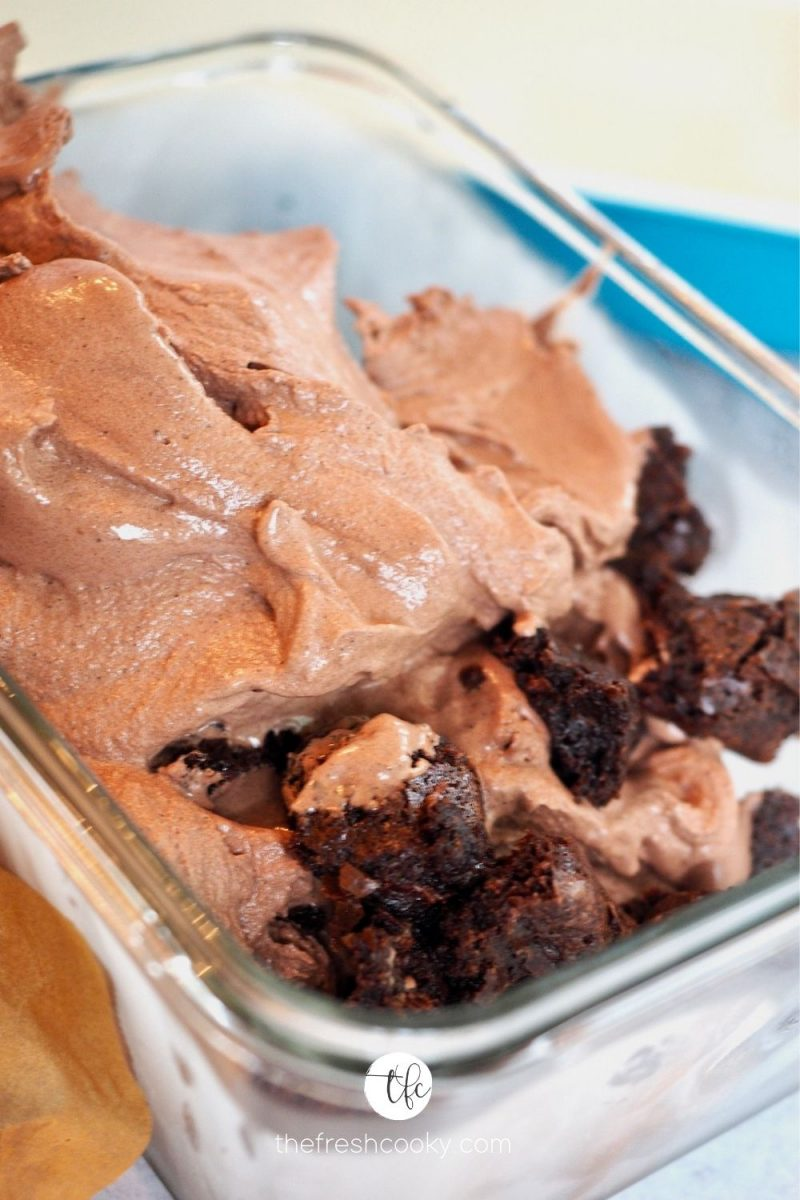 Process shot of combining chocolate ice cream and fudge brownie bites into storage container.