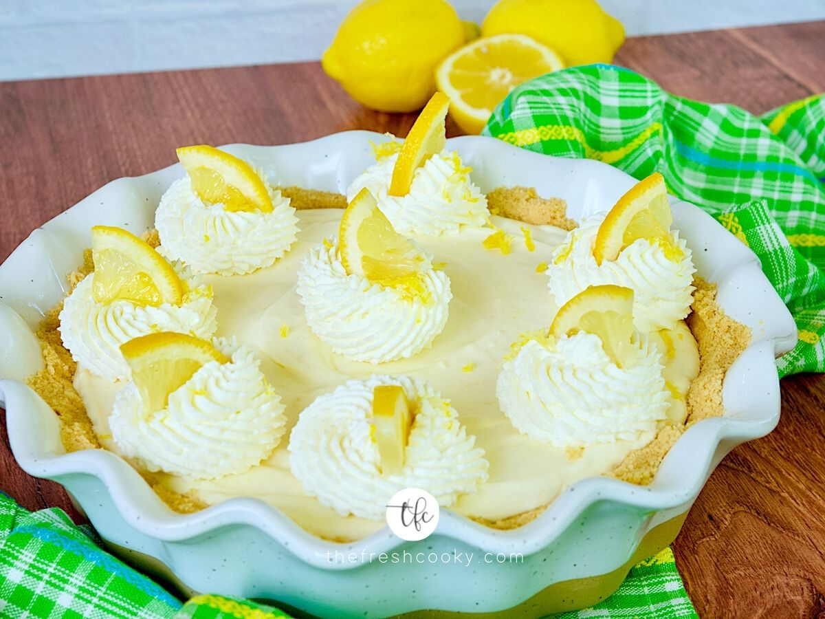 Lemon cream pie FB photo, with whipped cream dollups, decorated with a wedge of lemon with lemons in the background.