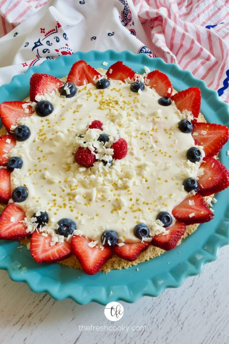 Patriotic Lemon Cream Pie decorated with sliced strawberries and blueberries and shaved chocolate with edible gold stars.