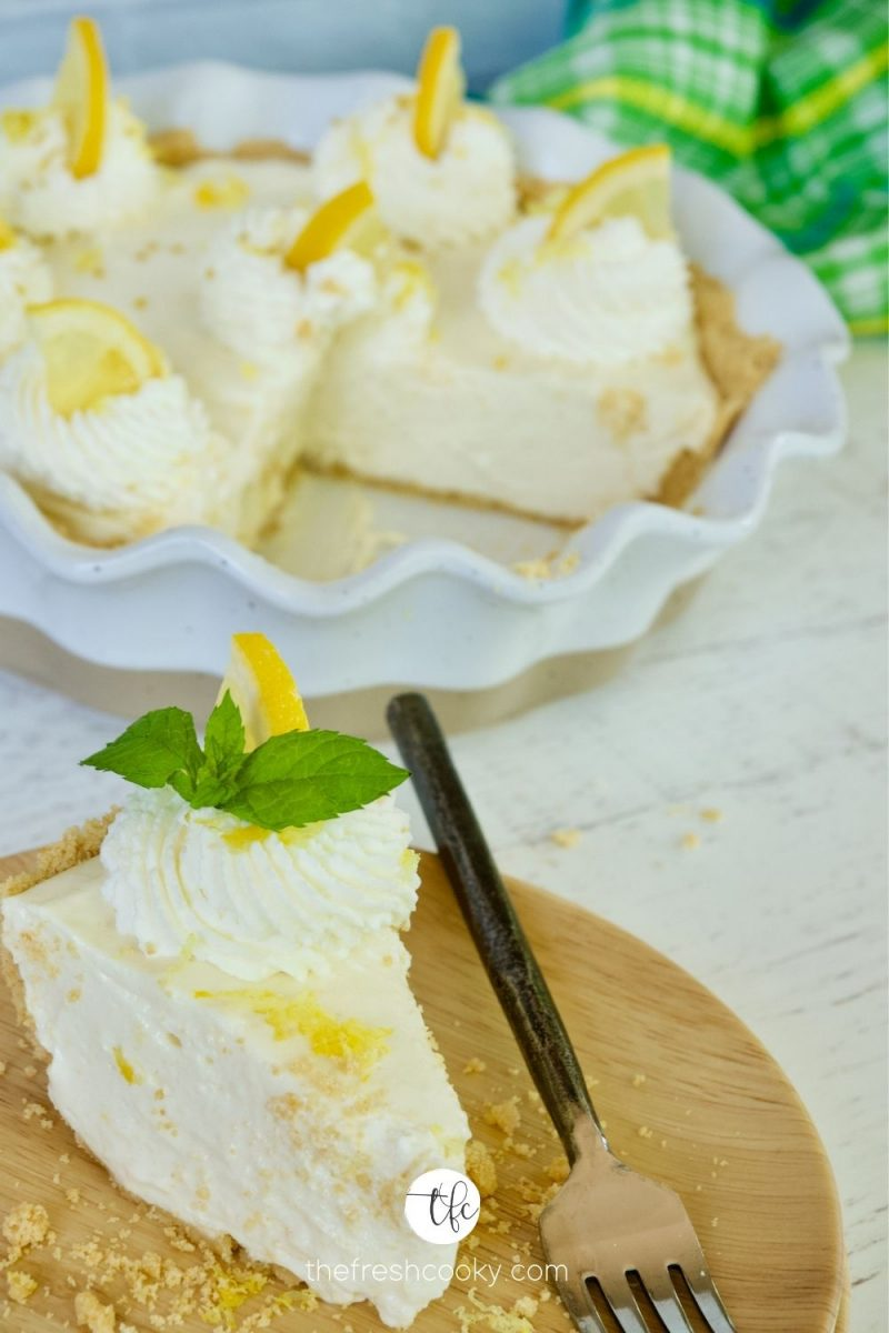 Lemon Cream Pie with slice on plate decorated with lemon zest, whipped cream and mint.