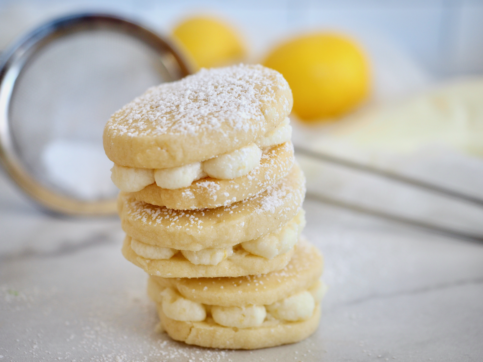 Lemon sandwich cookies three stacked on top of the other, with fresh lemons in background and seive with powdered sugar.