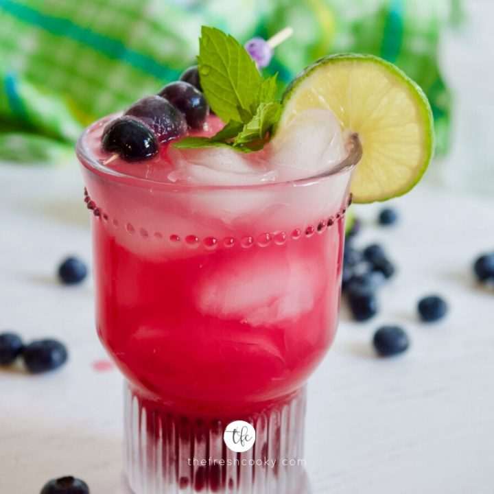 Image of a blueberry limeade drink in a pretty textured glass with a garnish of lime, mint and blueberries.