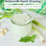 Buttermilk Ranch Dressing pin with image of glass jar of ranch dressing sitting on a wooden table with green onions, fresh basil and garlic cloves laying around.
