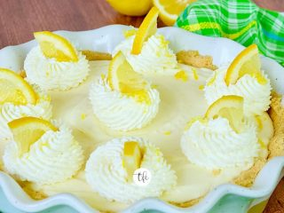 A full size Lemon Cream Pie square shot with wedges of lemon on top of dollops of whipped cream.