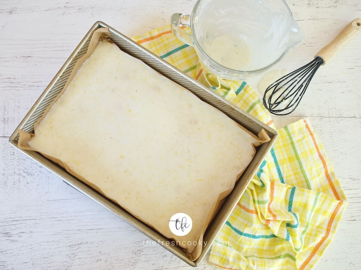 Top down image of glazed lemon bars in pan with whisk and bowl of glaze nearby.