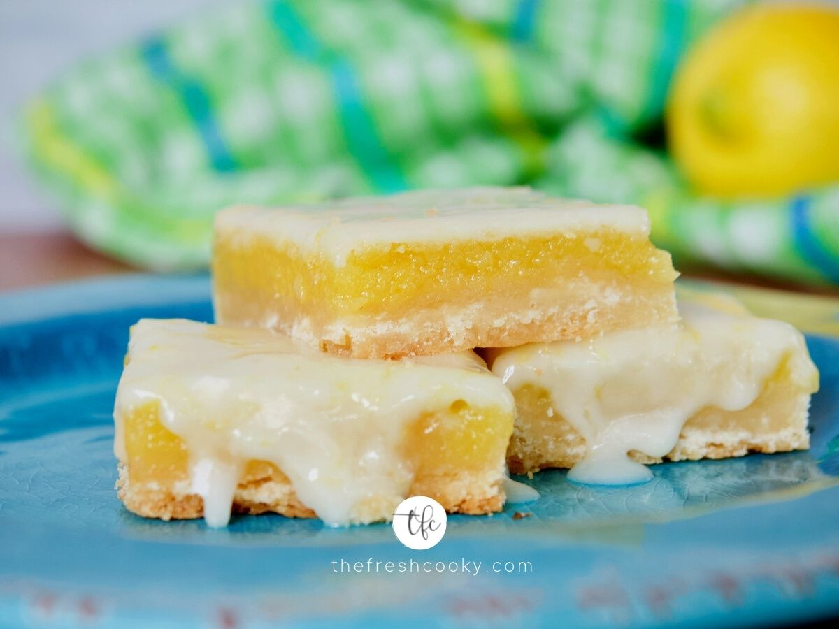 Facebook image of three stacked gooey old fashioned lemon squares with drippy glaze on top.