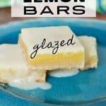 Easy Lemon Bars with tangy lemon glaze, image of three gooey lemon bars on blue plate with puddle of lemon glaze by one square.