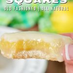 Easiest lemon squares recipe with a hand holding a lemon square with a bite taken out.