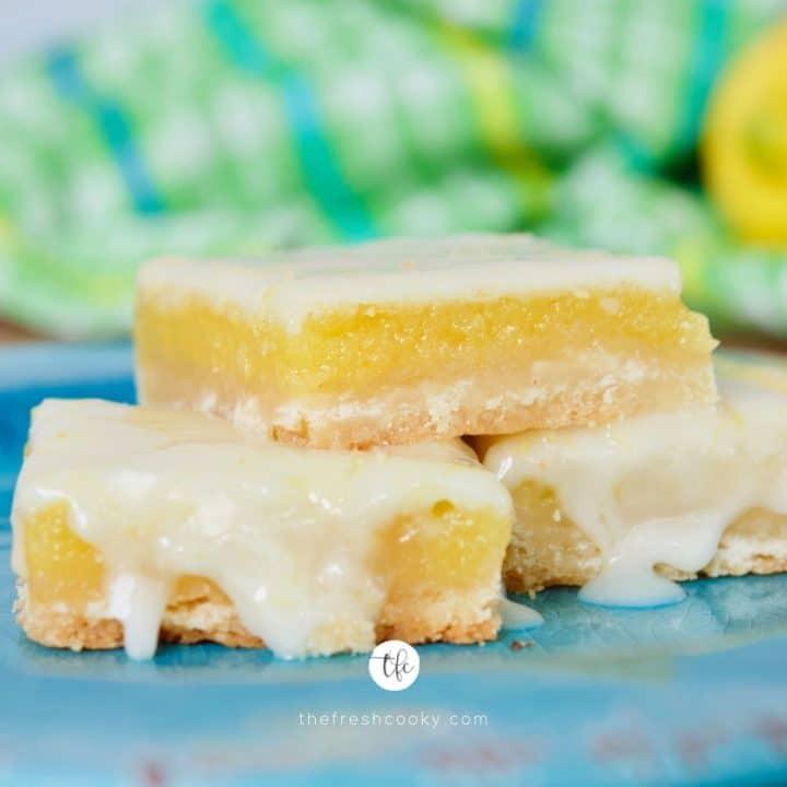 Square image of three stacked lemon bars with drippy lemon glaze.