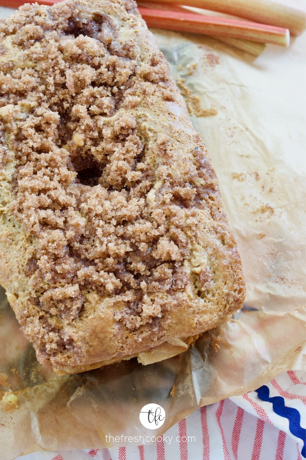 Loaf of Rhubarb bread with cinnamon crunch streusel topping sitting on parchment paper with rhubarb stalks behind.