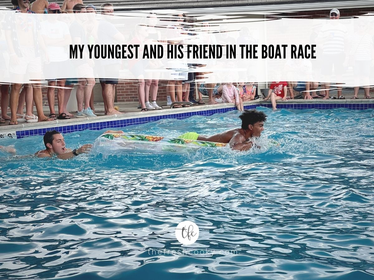 Two boys doing a raft race in the pool.