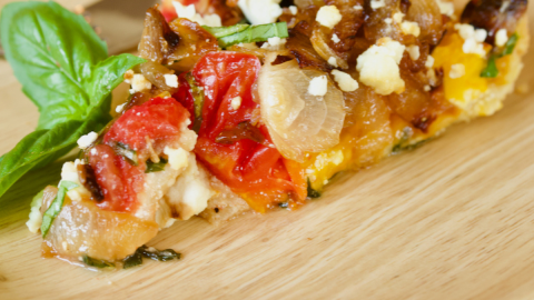 Slice of heirloom tomato pie on a plate with fresh basil and a rustic fork.