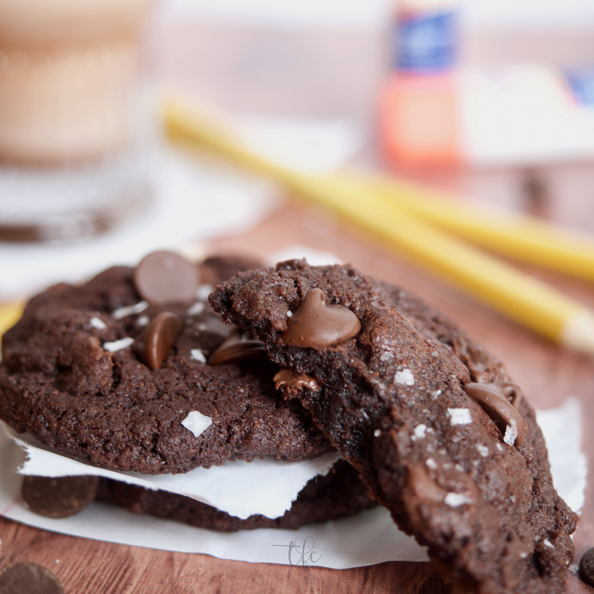 Triple Chocolate Cookies with one broken open to reveal a dark, fudgy center.