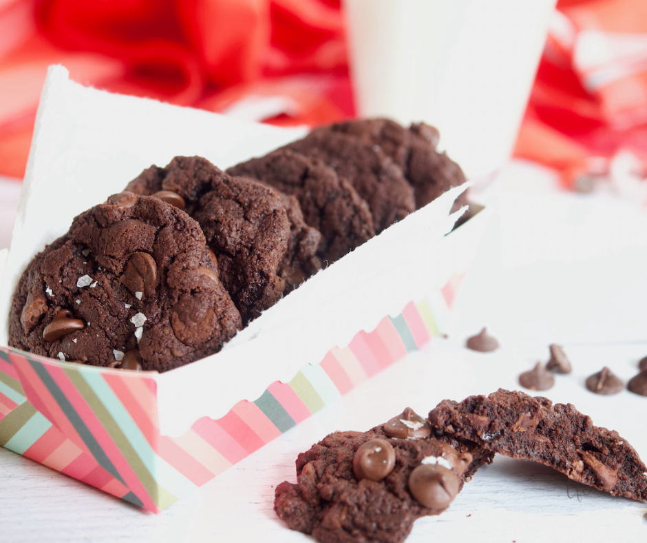 Chewy Triple Chocolate Cookies in a striped box with a cookie broken apart nearby.