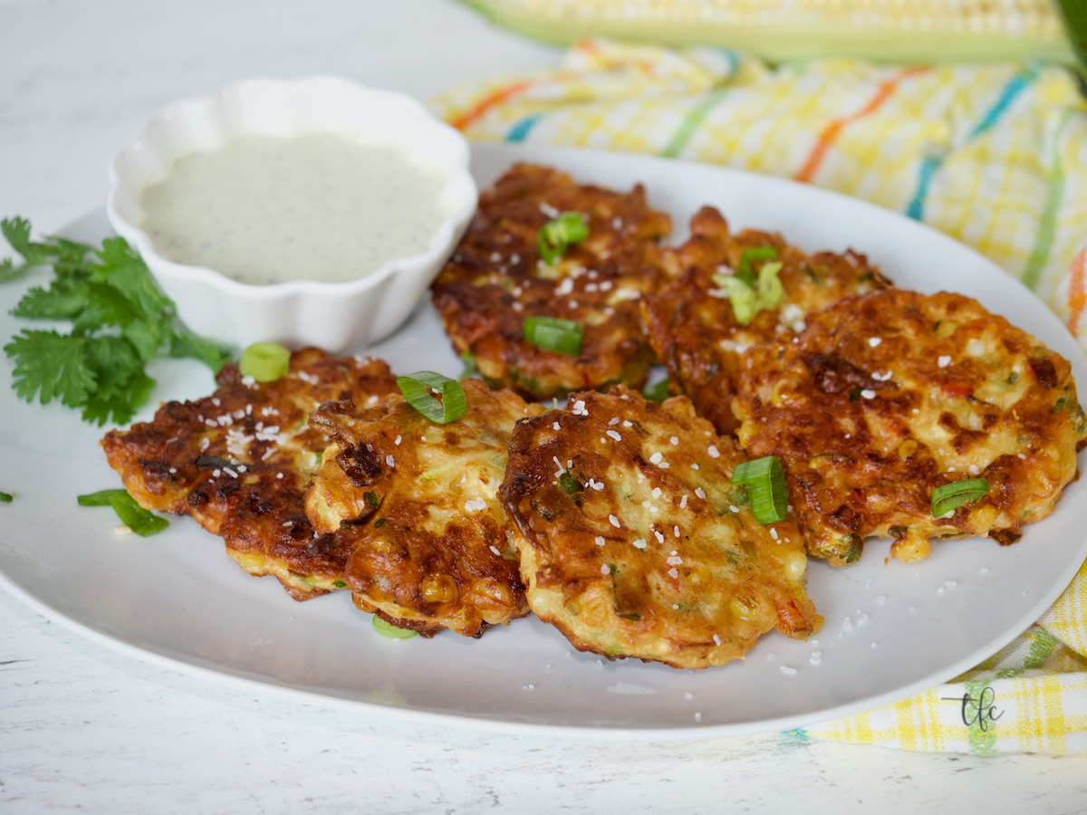 Facebook image of zucchini corn fritters on an oval plate with ranch dressing.