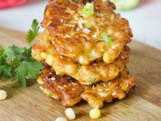 Zucchini Corn Fritters main image, three zucchini corn fritters stacked on one another with fresh veggies behind and cilantro beside.