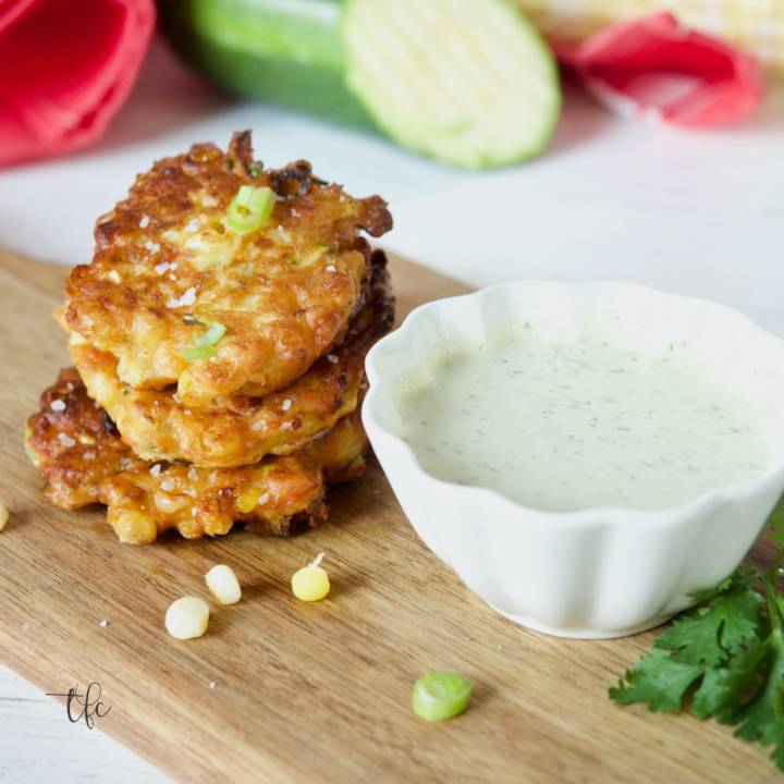 Easy Zucchini Corn Fritters sitting on a cutting board with a small bowl of ranch dressing nearby.